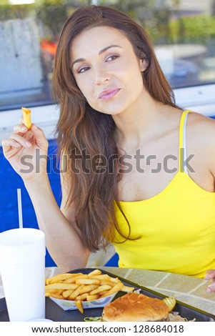 Young pretty woman having french fries at an outdoor cafe. Vertical Shot.
