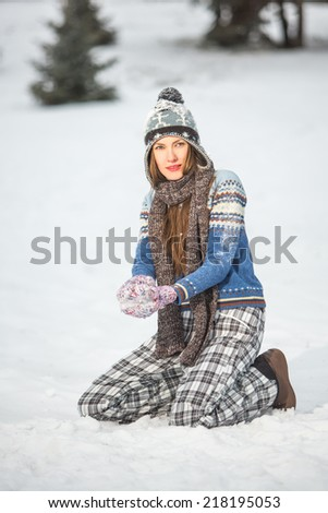 Young pretty woman having fun with snow in the wintertime