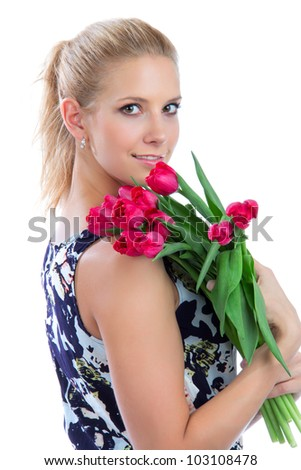 Young pretty woman holding a bunch of red tulips bouquet of flowers smiling on white background - stock photo