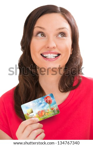 Young pretty woman holding plastic bank card and planning her spending - stock photo