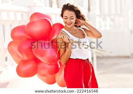 Young pretty woman holding red baloons-hearts. valentine day - stock photo