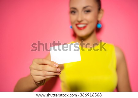 Young pretty woman holding white blank paper. Young smiling lady showing blank business card. Pink background. - stock photo