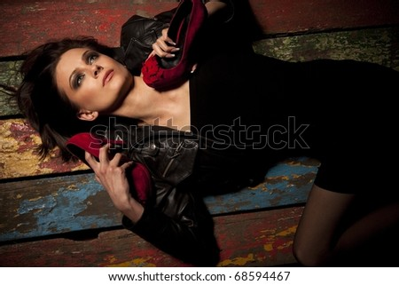 Young pretty woman holds red shoes with hands - stock photo