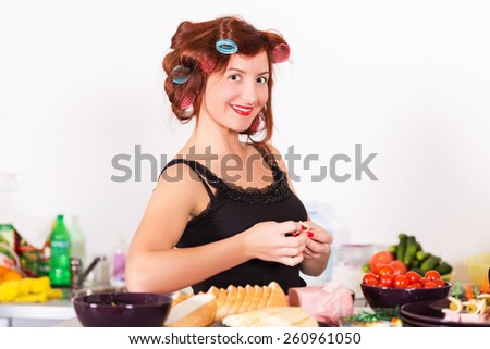 Young pretty woman housewife cooking with curlers on hair - stock photo