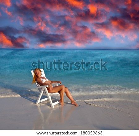 Young pretty woman in a beach chair at ocean