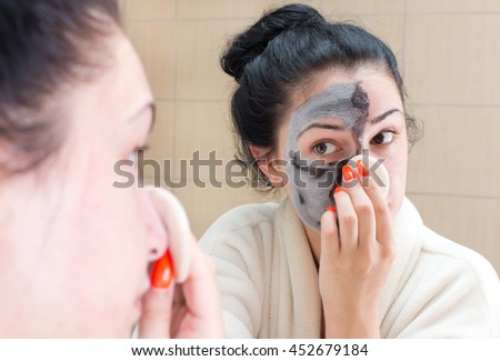 Young pretty woman in bathrobe removing facial mask in front of mirror in bathroom. Skin care and beauty concept - stock photo