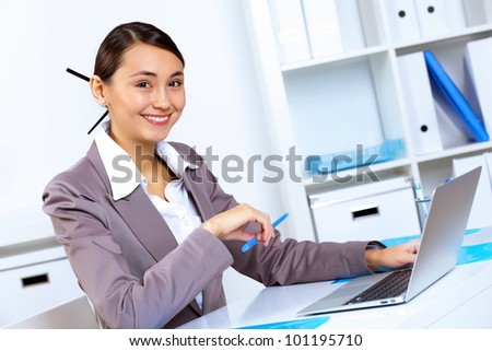 Young pretty woman in business wear working in office