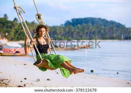 Young pretty woman in green skirt swinging at tropical beach - stock photo