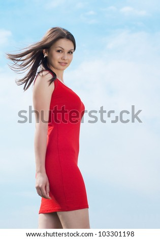 Young pretty woman in red dress against blue sky - stock photo