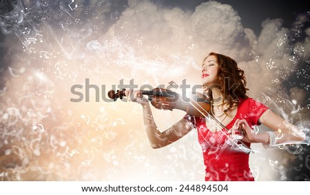 Young pretty woman in red dress playing violin - stock photo