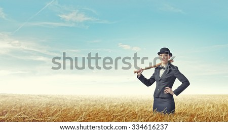 Young pretty woman in suit and hat with baseball bat