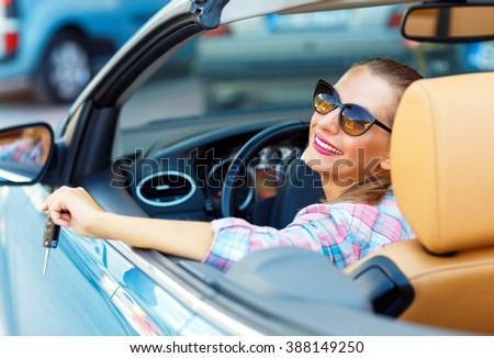 Young pretty woman in sunglasses sitting in a convertible car with the keys in hand - concept of buying a used car or a rental car - stock photo