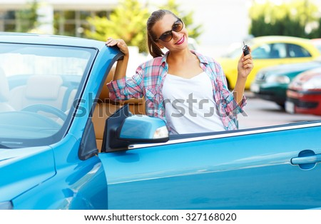 Young pretty woman in sunglasses standing near convertible with keys in hand - concept of buying a used car or a rental car - stock photo