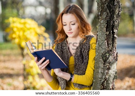 Young pretty woman in the park reading a book in autumn