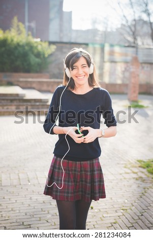 young pretty woman in town listening music with headphones - stock photo