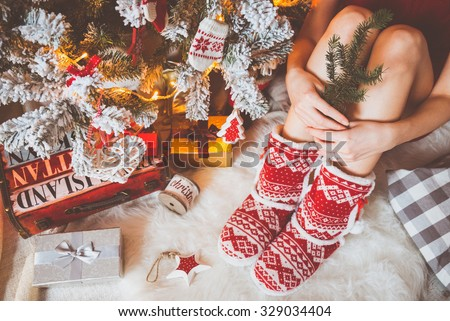 Young pretty woman in warm cozy clothes is sitting on the light wooden floor in her bright house near the christmas tree and holds a branch of fir in her hands. - stock photo