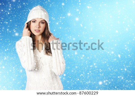 young pretty woman in winter dress over blue background with some snowflakes