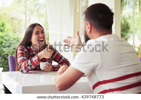 Young pretty woman is laughing and showing a thumb up gesture while chatting with her boyfriend on a terrace with garden view