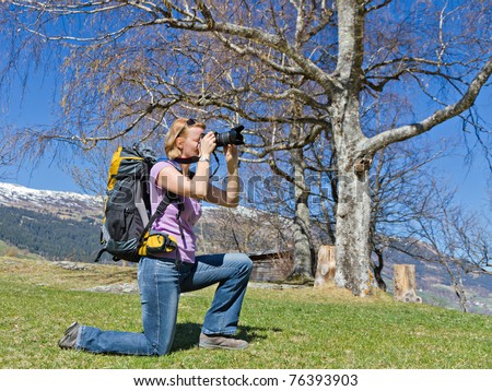 young pretty woman kneels in the mountains to get the perfect picture, dressed in hiking gear with backpack - stock photo