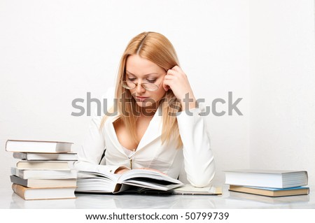 Young pretty woman learning at table with a lot of books, educational concept