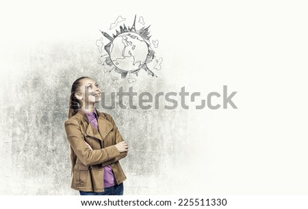 Young pretty woman looking at sketch of globe - stock photo
