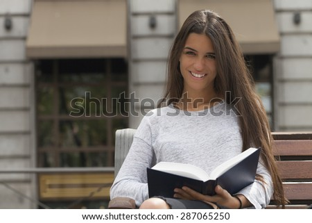 Young pretty woman looking at the camera with a book in her hands.  The lady is seating in a wooden bench in front of a city building.