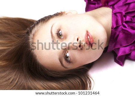Young pretty woman lying on the floor, close up, looking up, in pink dress - stock photo