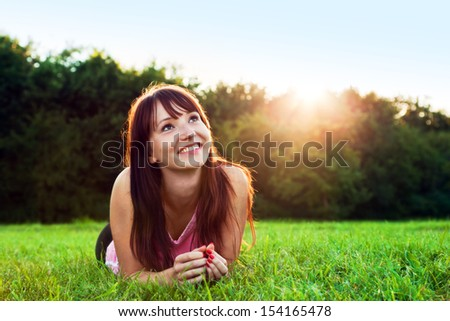Young pretty woman lying on the grass at summer sunset. Natural happiness, fun and harmony. - stock photo