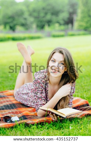Young pretty woman lying on the grass in the park and reading a book