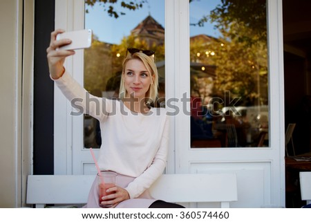 Young pretty woman making self portrait on mobile phone while resting in sidewalk cafe an drink beverage, charming female using cell telephone camera for take a picture of herself during her vacation  - stock photo