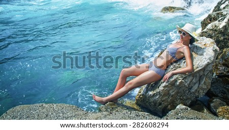 Young pretty woman on the beach sunbathing. Summer travel. Sea - water, wellbeing. Relaxed girl sunbathe in bikini wearing sunglasses and hat.  Copay space - copyspace - stock photo