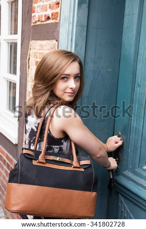 Young pretty woman opens the front door