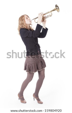 young pretty woman playing the trumpet against white background
