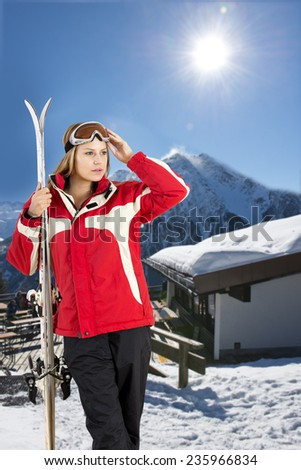 young, pretty woman posing with her skis in front of a hill top restaurant in a ski resort - stock photo