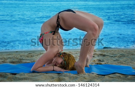 Young pretty woman practicing yoga on the beach by the ocean  - stock photo
