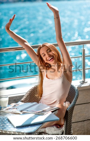 Young pretty woman raising up hands on the balcony near the sea. Good morning concept - stock photo