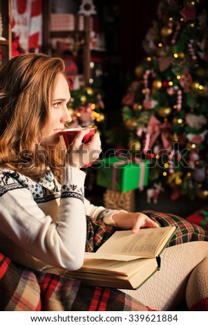 young pretty woman reading a book and holding a cup with christmas tree on background - stock photo
