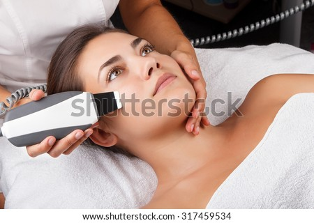 Young pretty woman receiving treatments in beauty salons. Young beautiful dark-haired woman in the office beautician lying on the couch. Ultrasonic cleaning procedure. Hardware cosmetology. - stock photo