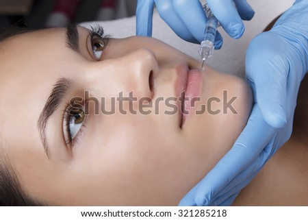 Young pretty woman receiving treatments in beauty salons. Young beautiful dark-haired woman in the office beautician lying on the couch. Contouring procedure , revitalization. Beauty injections . - stock photo