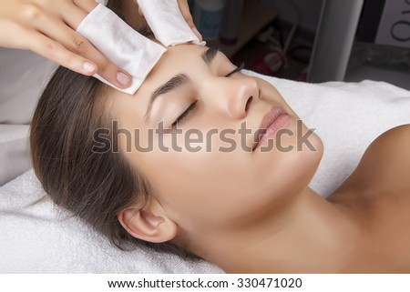 Young pretty woman receiving treatments in beauty salons. Young beautiful dark-haired woman in the office beautician lying on the couch. The procedure for cleaning the face - stock photo