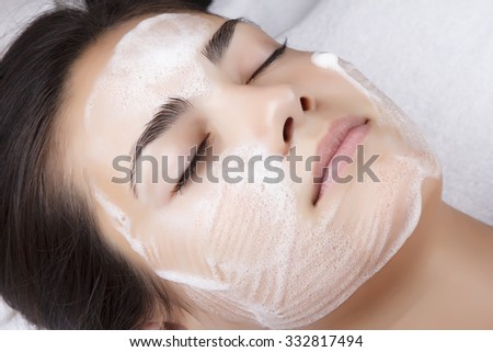 Young pretty woman receiving treatments in beauty salons. Young beautiful dark-haired woman in the office beautician lying on the couch. Facial cleansing foam using.