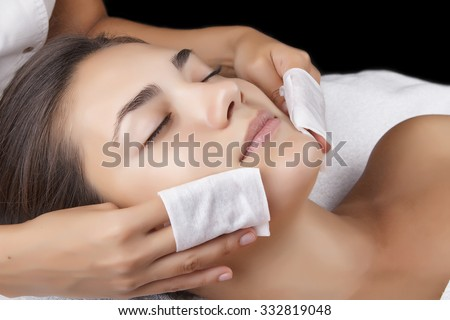 Young pretty woman receiving treatments in beauty salons. Young beautiful dark-haired woman in the office beautician lying on the couch. Massage procedure. - stock photo