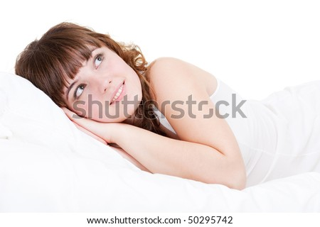 young pretty woman relaxing in the bed over white background