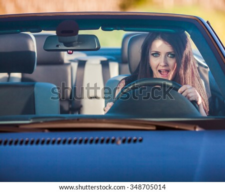 Young pretty woman scared in the car - stock photo
