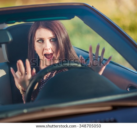 Young pretty woman scared in the car