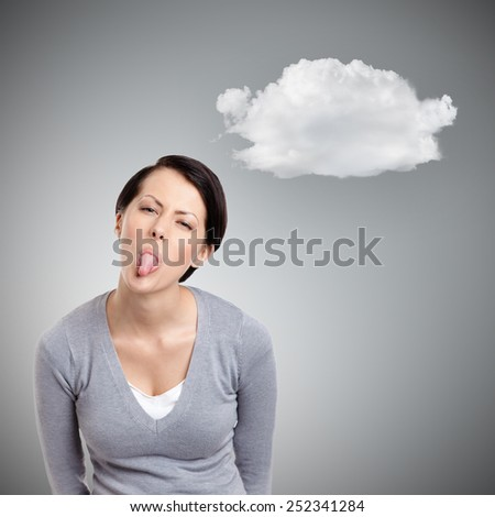 Young pretty woman shoots out tongue,  grey background