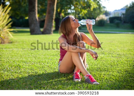 Young pretty woman sitting and drinking water on a grass - stock photo