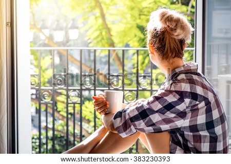 Young pretty woman  sitting at opened window drinking coffee and looking outside enjoys of rest. Dream