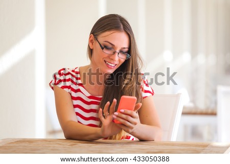 Young pretty woman sitting in a cafe with a smartphone - stock photo