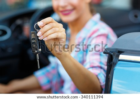 Young pretty woman sitting in a convertible car with the keys in hand - concept of buying a used car or a rental car - stock photo